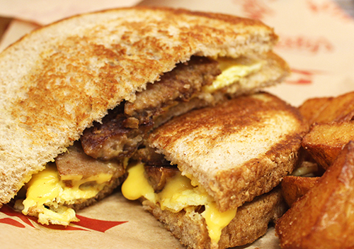 Photo of sausage, egg and cheese grilled sandwich with home fried potatoes