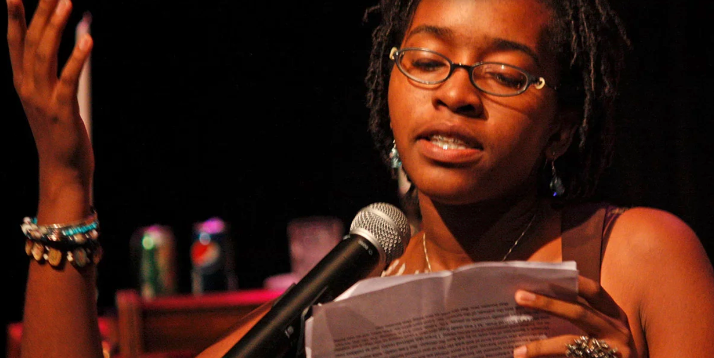 Photo of a woman reading poetry from a typed sheet. Her face is expressive, right hand raised