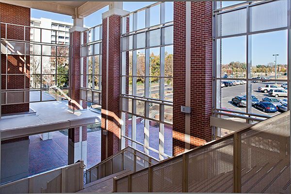 Photo taken from inside staircase of South Village deck, looking out upon one of the high rise residence hall
