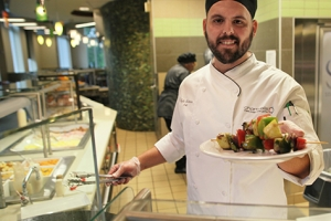 Chef Kyle holds up fresh plate of shish kabobs