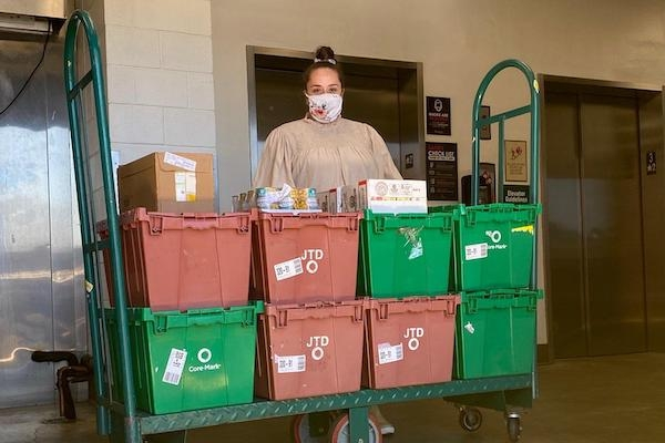 Staff member stands with donated food bins
