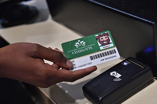 Photo of student's hand tapping 49erCard at card reader to enter dining hall