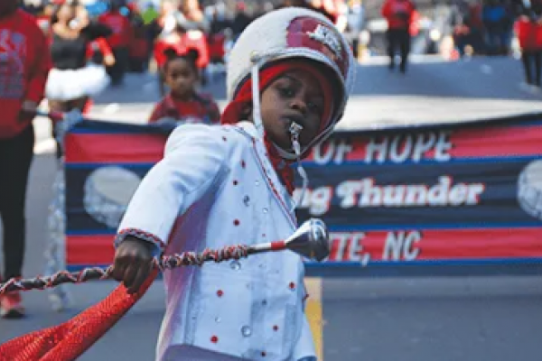 Photo of young boy in band uniform, leading a parade